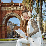 smiling elegant woman in earmuffs in Barcelona, Spain with map