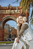 happy trendy woman in earmuffs in Barcelona, Spain with map
