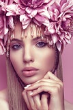 Beautiful woman with flower crown and makeup on pink background