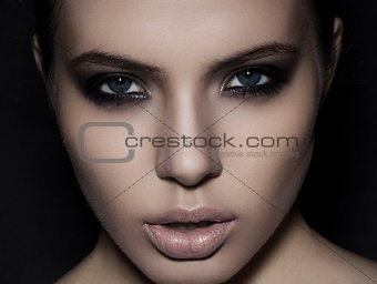 Beautiful woman model smokey eyes makeup closeup on black
