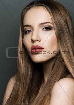Beautiful woman model portrait with long hair on dark background