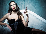 Attractive young woman lying on sofa and smoking cigarette. Retro style