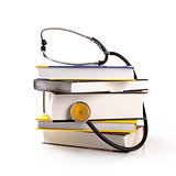 medical education - stack of books with stethoscope on white