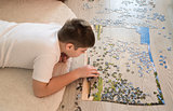 Teen boy collects a puzzle lying on carpet