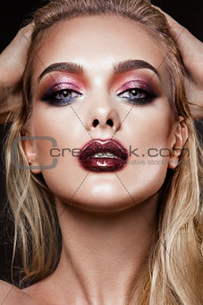 Portrait of beautiful young woman with colored make-up