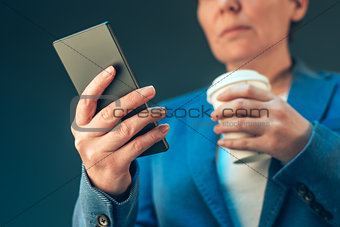 Satisfied businesswoman drinking coffee to go and looking mobile
