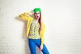 Fashion Hipster Girl at White Brick Wall