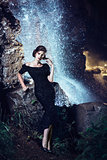 Woman posing near waterfall.