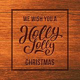 Holly Jolly text on wood. Christmas greeting card