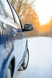 Close up Image of Side Rear-view Mirror on a Car in the Winter Landscape with Evening Sun