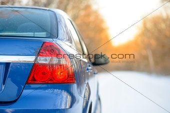 Blue Car on the Winter Snowy Road at Sunset. Close up Rear View. Travel and Drive Safe Concept.