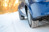 Close-up Image of Winter Car Wheel on Snowy Road. Drive Safe Concept.