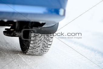 Close-up Image of Winter Car Tire on Snowy Road. Drive Safe Concept.