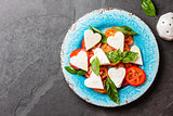 Caprese salad with tomatoes, cheese hearts, basil. Valentine day menu