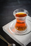 Transparent cup of thin glass and black tea. Spoon.