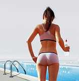 woman near swimming pool with water