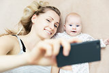 mother and little infant baby taking selfie with phone in bed