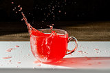 Juice in a Cup and splash with spray on  dark background