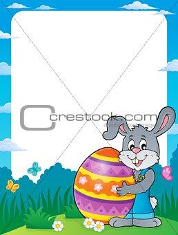 Frame with bunny holding big Easter egg