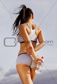 back of athletic woman with bottle