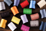 Colorful cotton reels scattered on dark wood