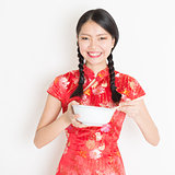 Oriental female in red cheongsam eating with chopsticks