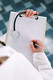 Female doctor in white uniform writing on clipboard paper