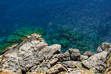 View from above on transparent blue sea water and rocks