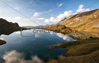 alpine lake with reflected blue sky