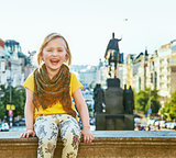 smiling child on Wenceslas Square in Prague sitting on parapet