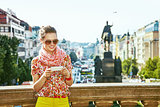 traveller woman on Vaclavske namesti in Prague writing sms