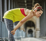 active woman catching breath after exercise on bridge in Paris