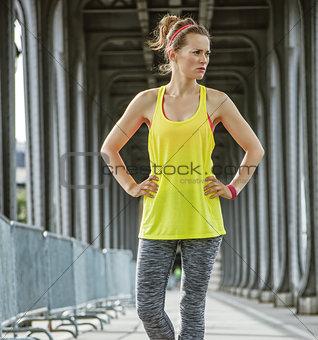 active woman standing on Pont de Bir-Hakeim bridge in Paris