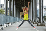 active woman stretching on Pont de Bir-Hakeim bridge in Paris