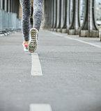 Closeup on woman jogger running on Pont de Bir-Hakeim bridge