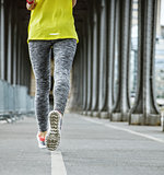 Closeup on woman jogger running on Pont de Bir-Hakeim bridge