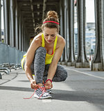 sportswoman tying shoelaces on Pont de Bir-Hakeim bridge, Paris