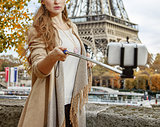 woman taking selfie using selfie stick on embankment in Paris