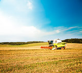 Combine Harvester in the Oat Field. Agriculture.