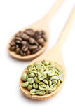 green and black coffee beans in wooden spoon