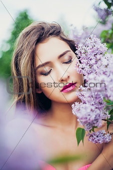 Portrait of young beautiful woman posing among lilac. Closed eyes.