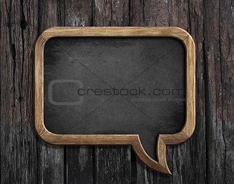 chalkboard in shape of speech bubble on wooden background