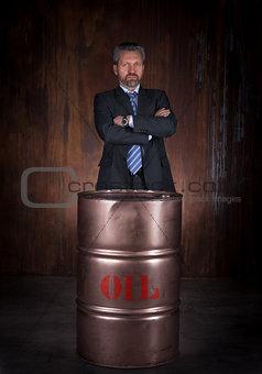 Mature businessman and barrel of crude oil on dark background