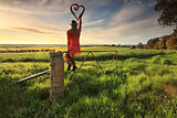Escape to the Country - female on fence with love heart in morni