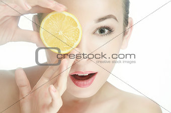 beauty, young woman with one halves of a lemon