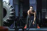 Powerful attractive muscular Fitness trainer do battle workout with ropes