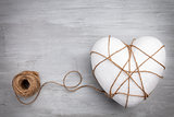 Heart bound by a string on grey background