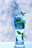 Mint drink with ice and leaves on sky background