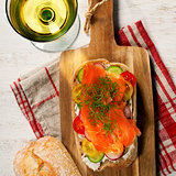 Sandwich with salmon, cucumber, cream cheese, dill and tomatoe