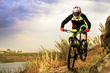 Professional Cyclist Riding the Bike at the Rocky Trail. Extreme Sport Concept. Space for Text.